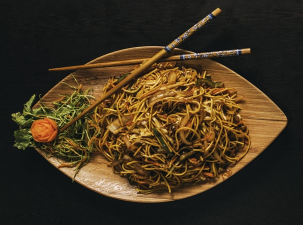 A noodle dish on a wooden plate with chopsticks